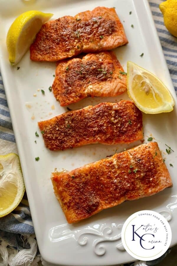 Top view of a white platter filled with four salmon filets with lemon wedges and logo on the right corner.