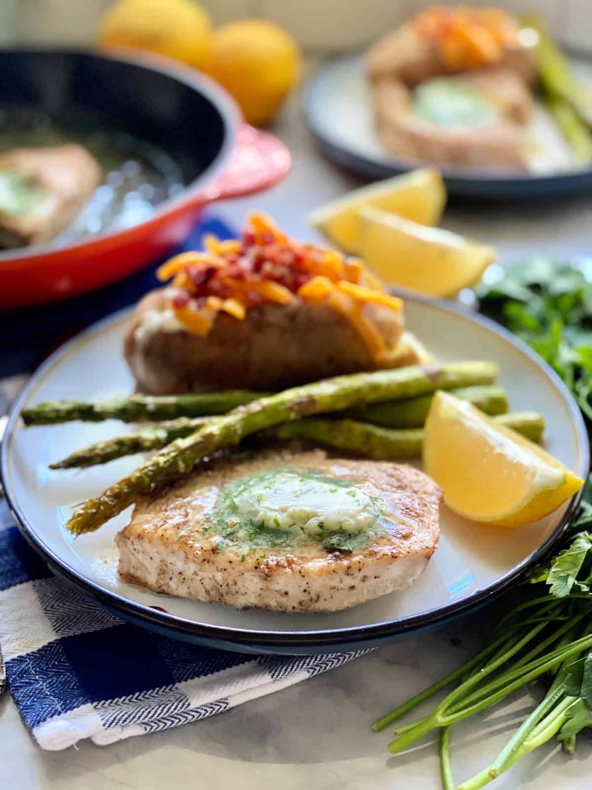White plate filled with a swordfish steak with butter, asparagus, and a baked potato.