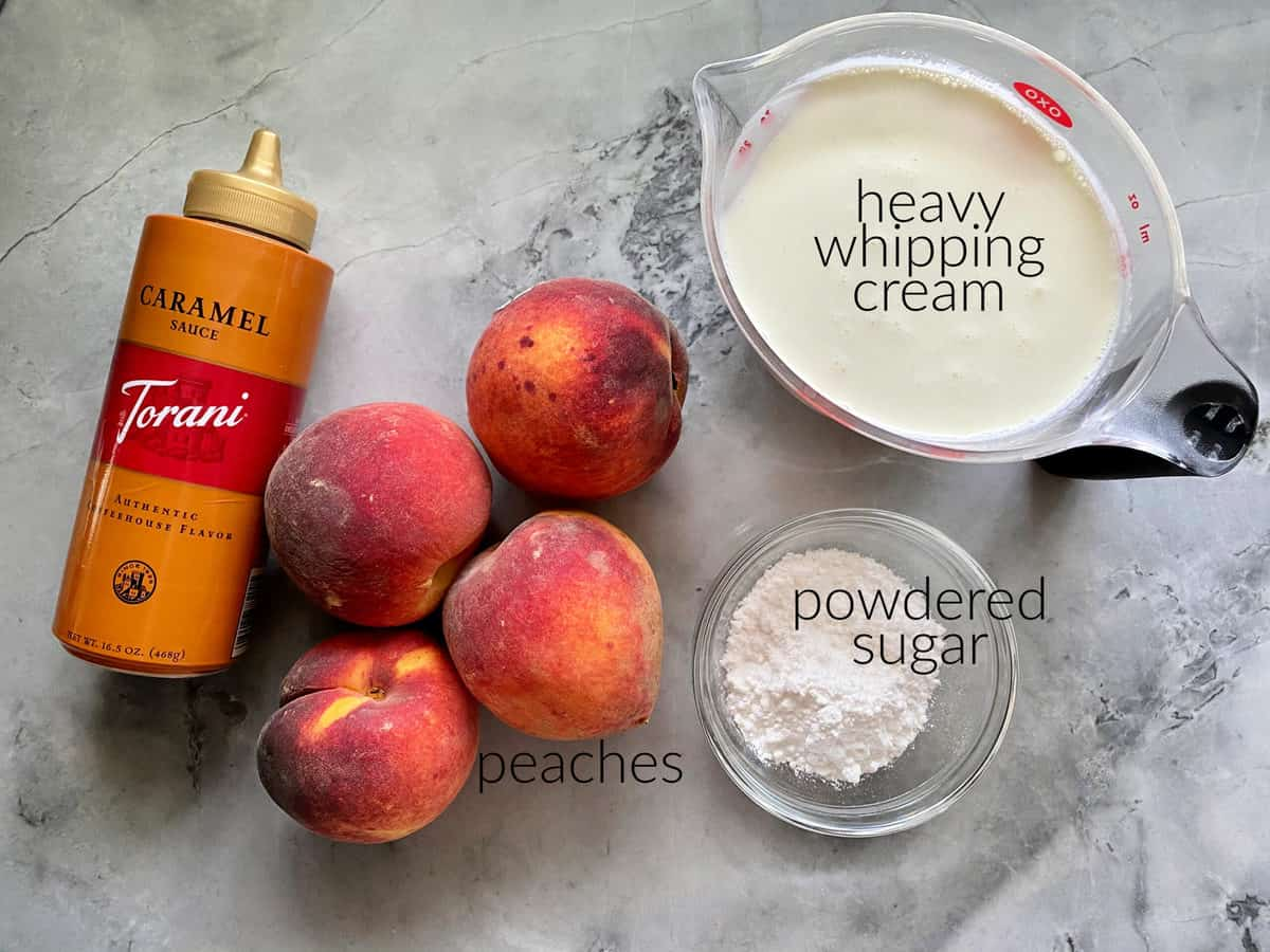 Ingredients on marble countertop: caramel sauce, peaches, whipping cream in measuring cup, and powdered sugar.