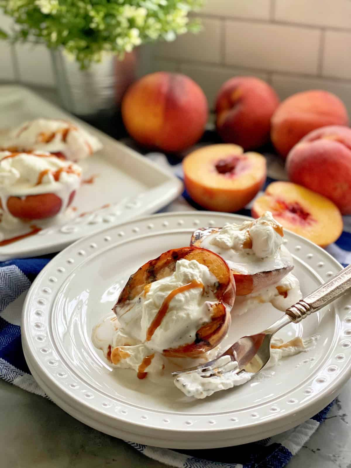 Two white plates stacked topped with grilled peaches and cream with peaches in background.