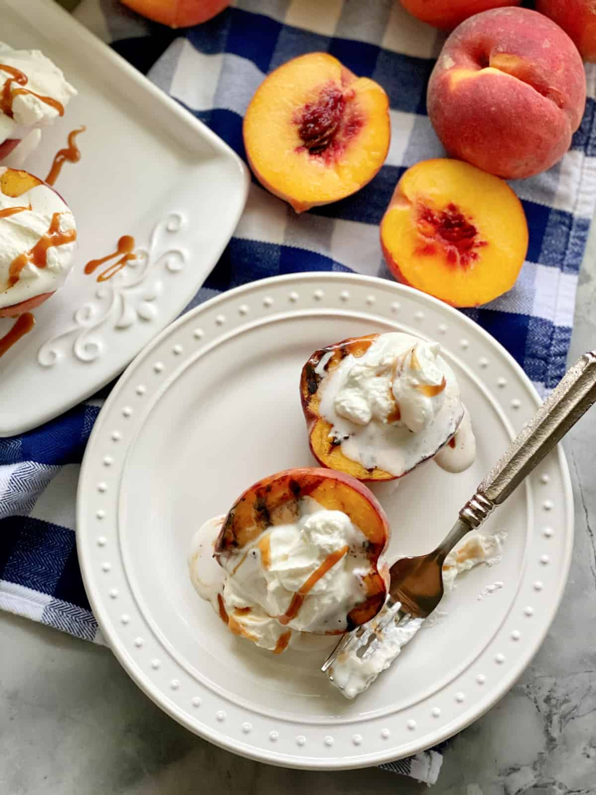 Top view of two grilled peaches on a white plate topped with whipped cream and caramel sauce.