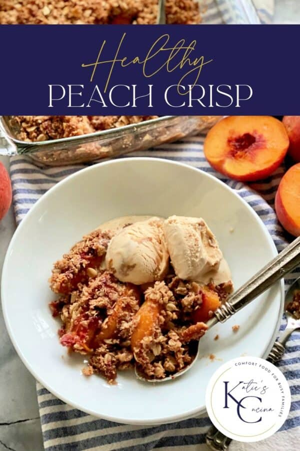 Shallow white bowl filled with ice cream, peach crisp, and a spoon with recipe title text on image for Pinterest.