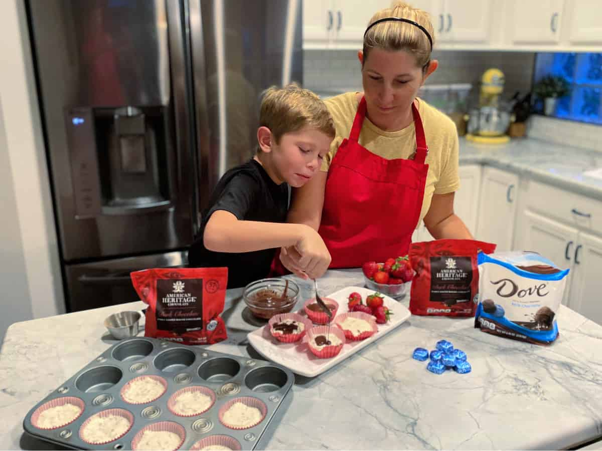 Mother and son preparing mini cheesecakes with a chocolate topping.