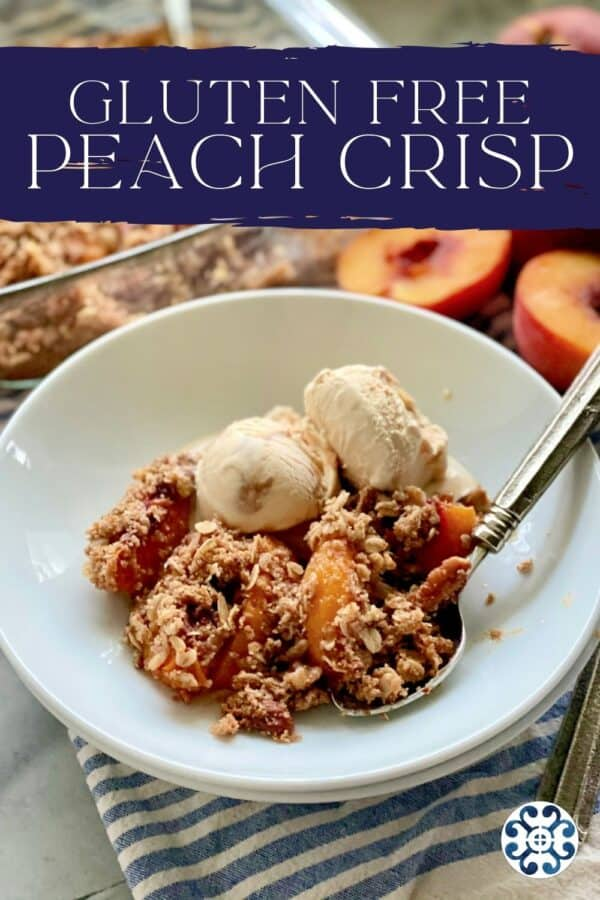 White shallow bowl filled with caramel ice cream, peach crisp, and spoon with peaches in background and recipe title text on image for Pinterest.