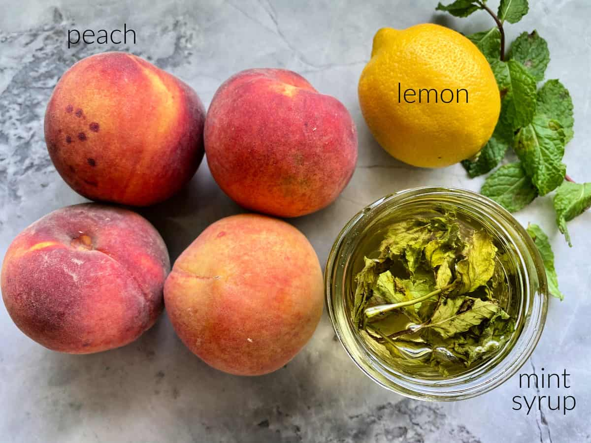 Ingredients on marble counter: peaches, lemon, mint syrup.