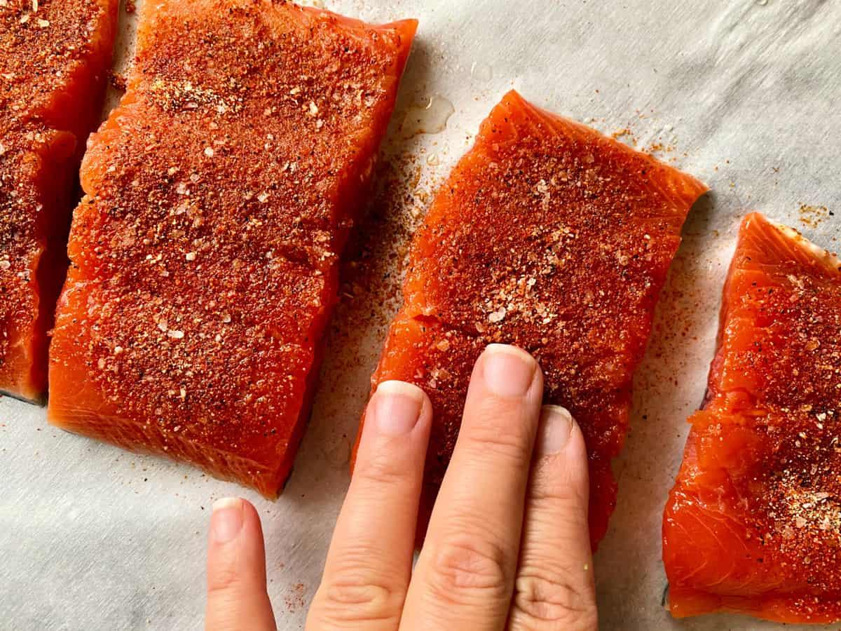 Top view of female hand rubbing seasoning on salmon filets.