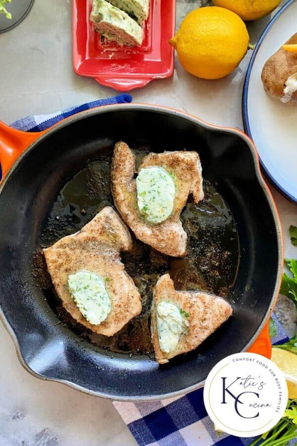 Top view of an orange cast iron skillet filled with 3 swordfish steaks topped with herb butter with logo on the right corner.