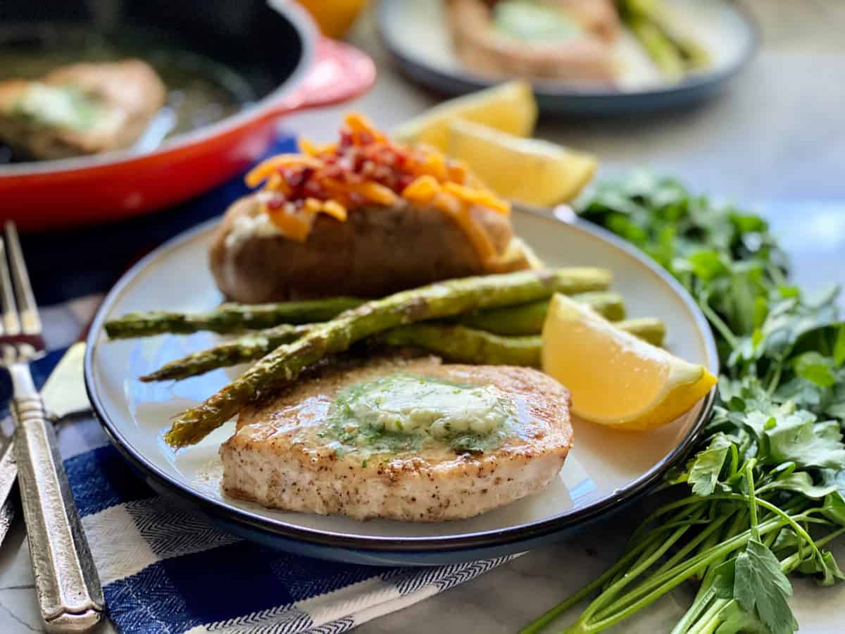 Round plate with Swordfish Steak wedge of lemon, asparagus spears and loaded baked potato.