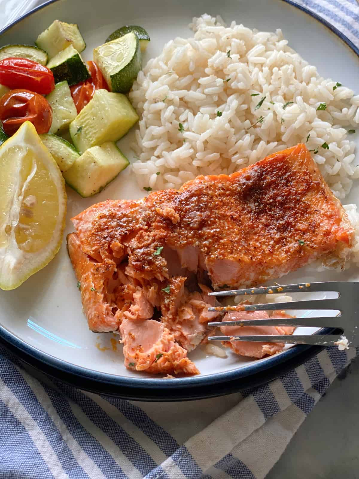 White plate filled with white rice, zucchini, tomatoes, a lemon wedge and a fork flaking cooking salmon.