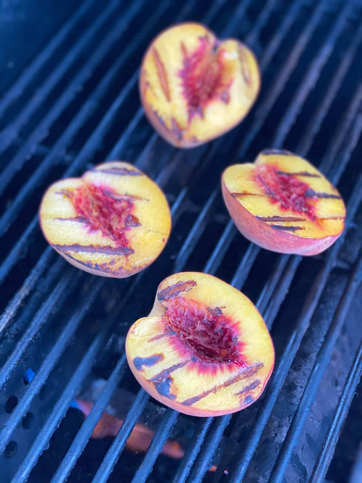 Four peaches with grill marks on grill grates with fire underneath them.