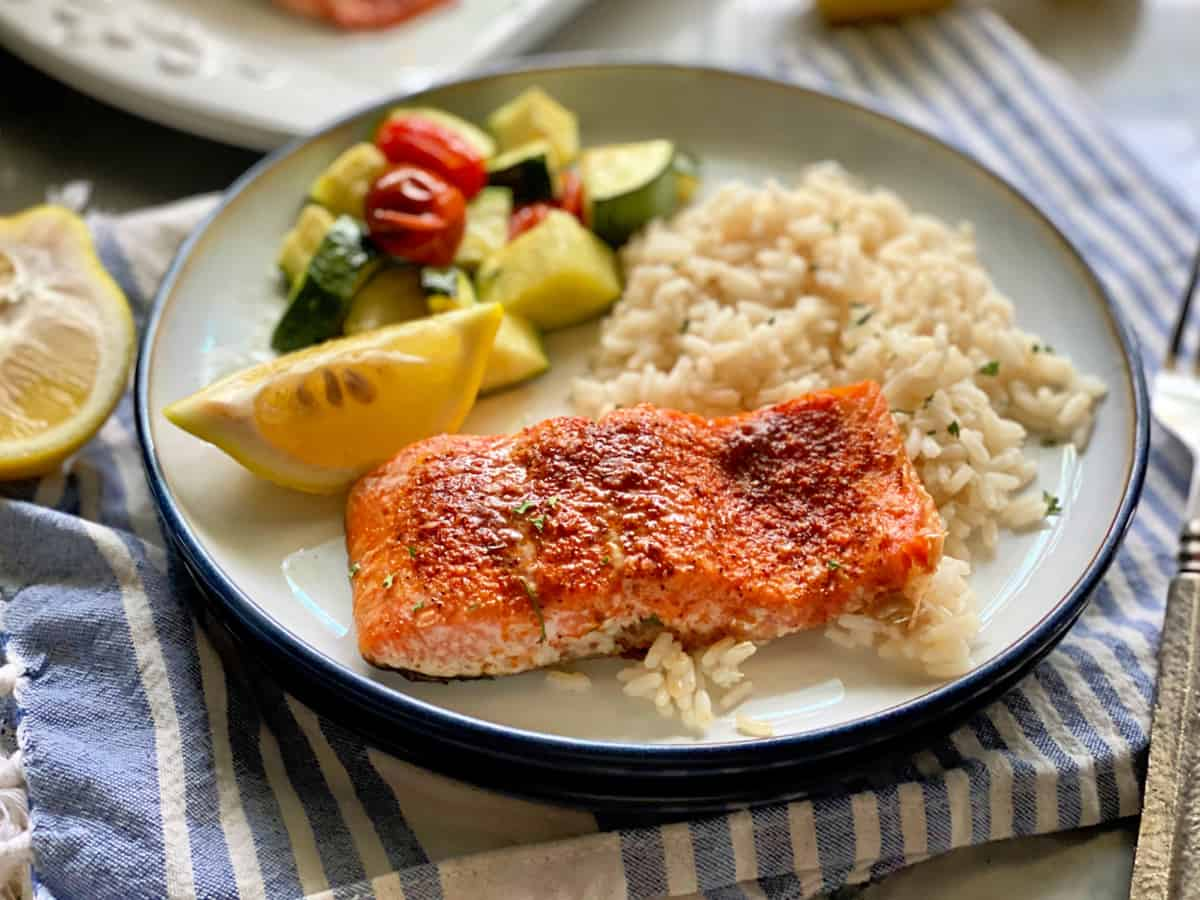 White plate filled with salmon filet, lemon wedge, white rice, and zucchini.