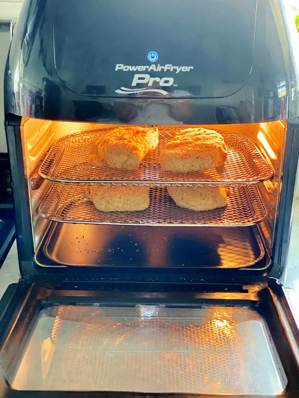 Power AirFryer Pro with two metal racks with breaded pork chops inside.