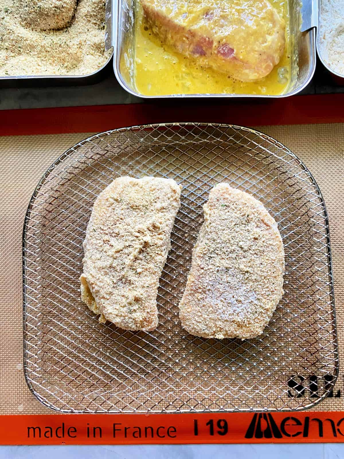 Top view of breaded pork chops on a wire rack sitting on a silicone SILPAT mat.