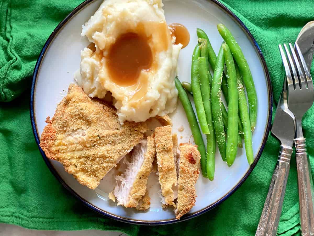 Top view of a white plate with sliced pork chop, mashed potato with gravy, and green beans.