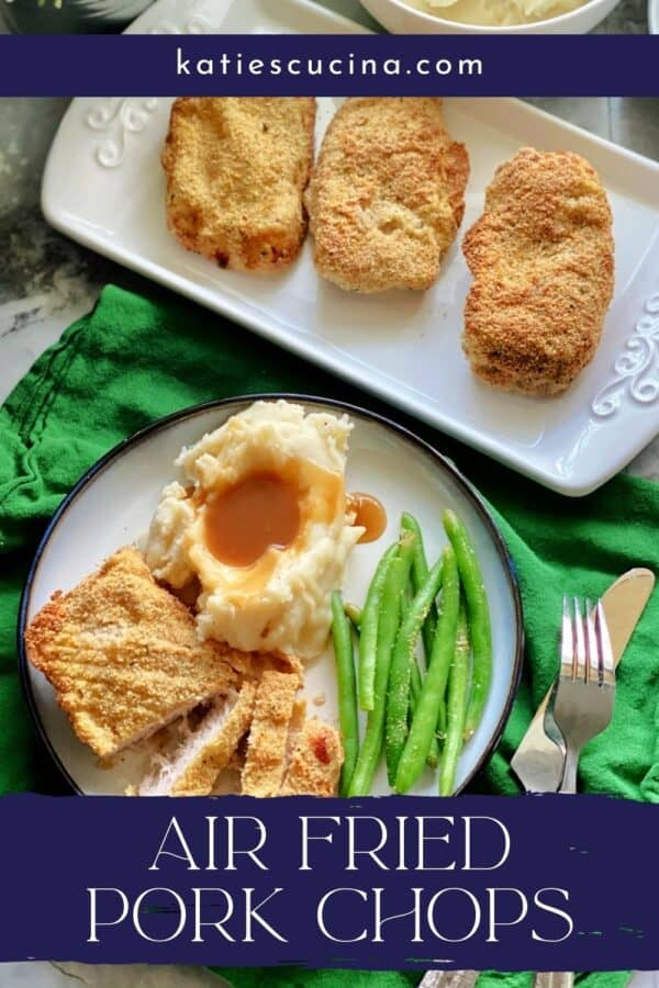 Top view of a white plate filled with pork chop, mashed potatoes, gravy, and green beans with recipe title text on image for Pinterest.