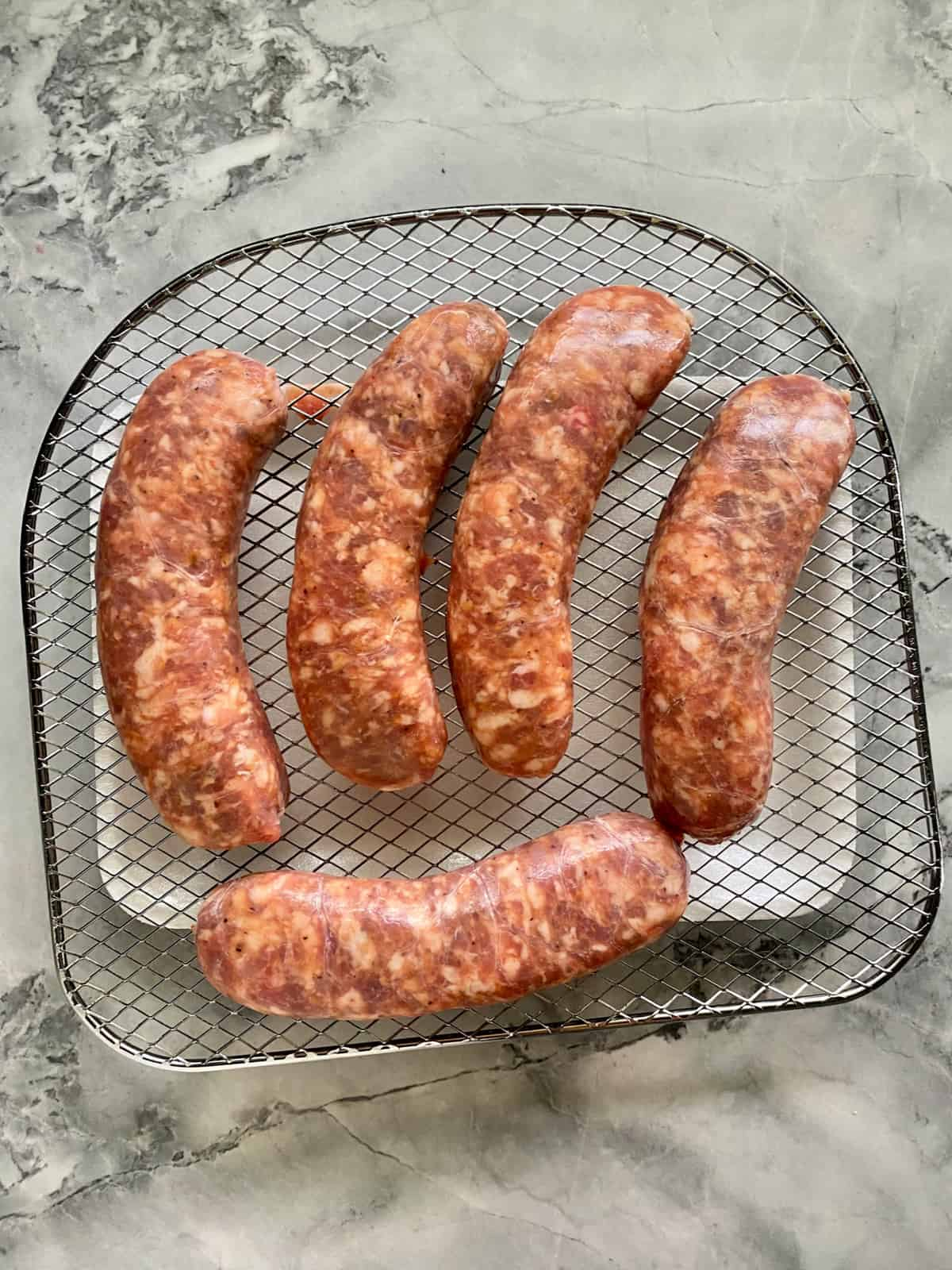 Top view of five raw sausage links on a wire rack.