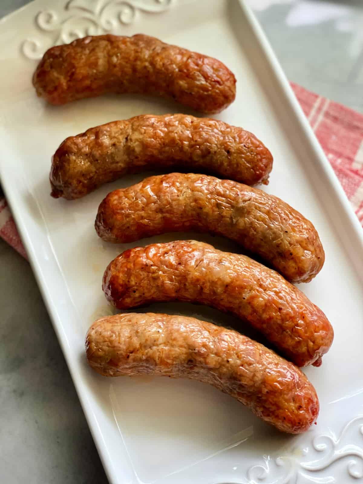 Top view of 5 crispy sausage links on a white platter with red and white striped napkin underneath it