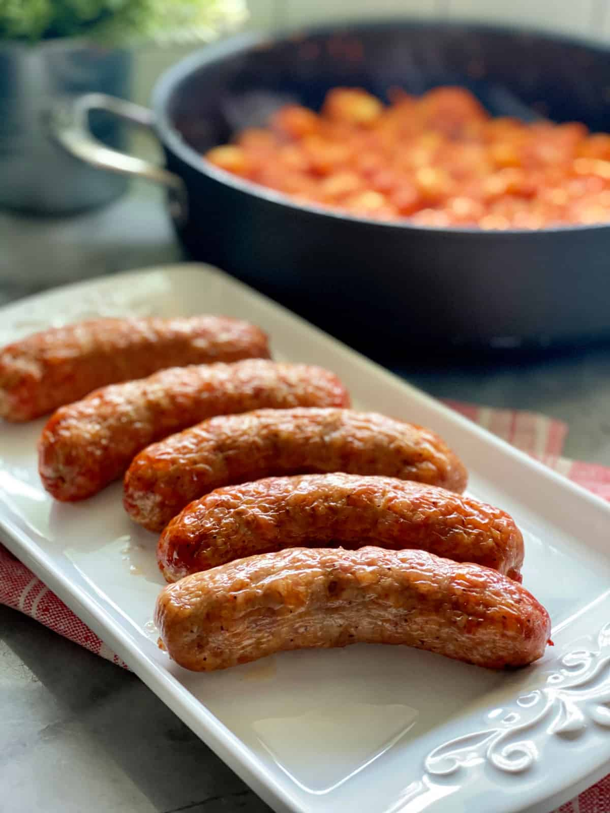 White platter filled with crispy sausage links with tomato red sauce in a skillet in background.