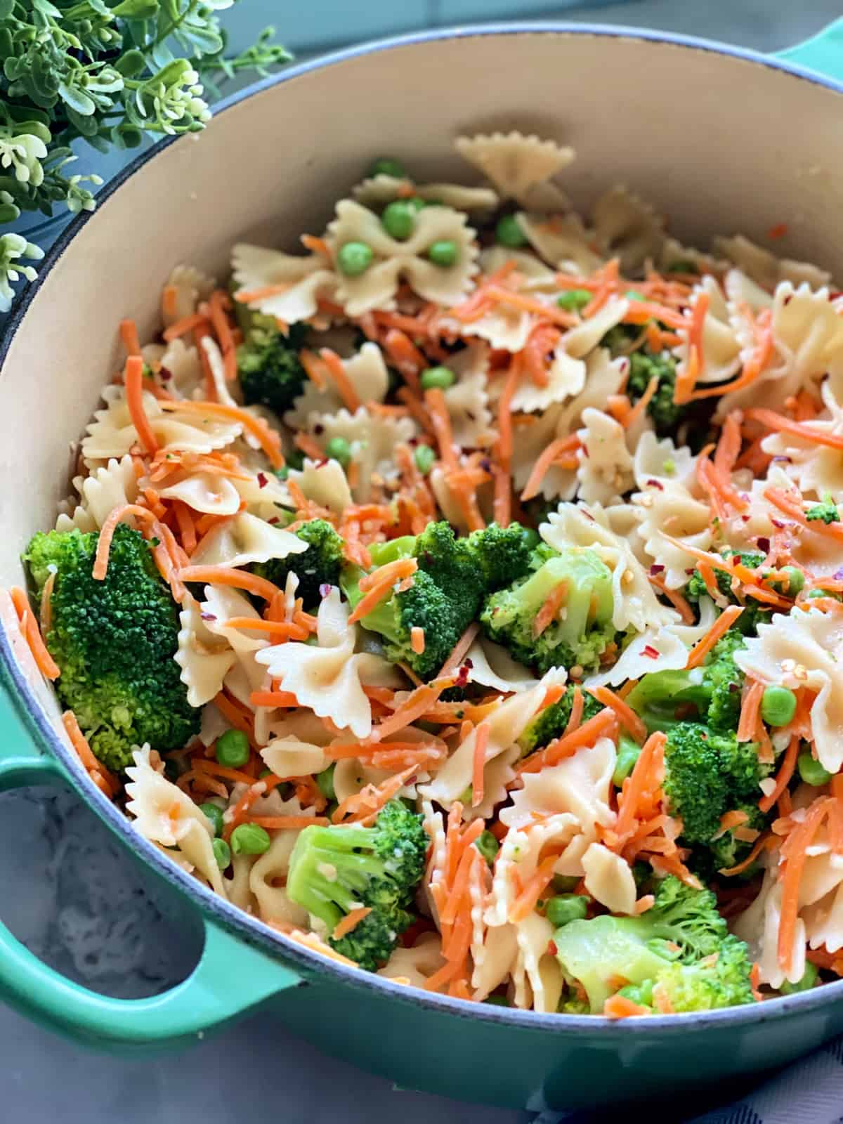 Green pot filled with bow tie pasta, shredded carrots, broccoli, green peas, and red pepper flakes.