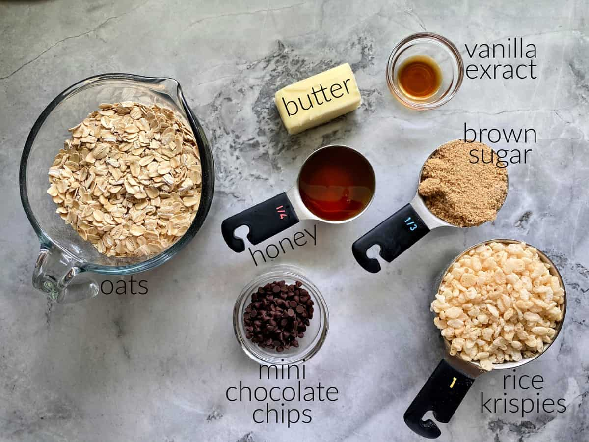 Ingredients on marble countertop: oats, butter, honey, vanila extract, brown sugar, chocolate chips, and rice krispies.