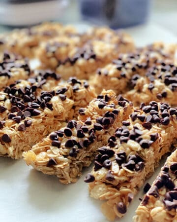 Homemade granola bars with mini chocolate chips lined up on parchment papered countertop.