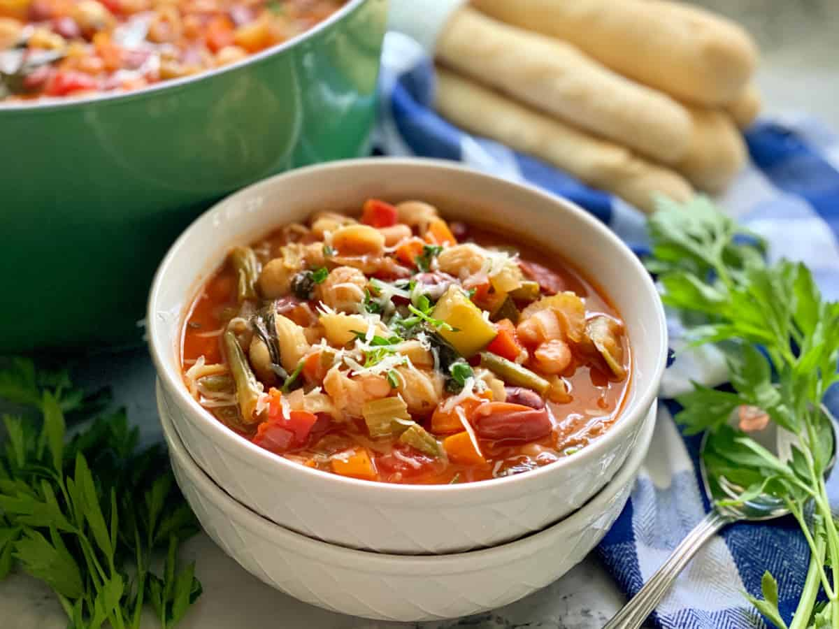 Two white bowls stacked filled with minestrone soup topped with shredded cheese and parsley.
