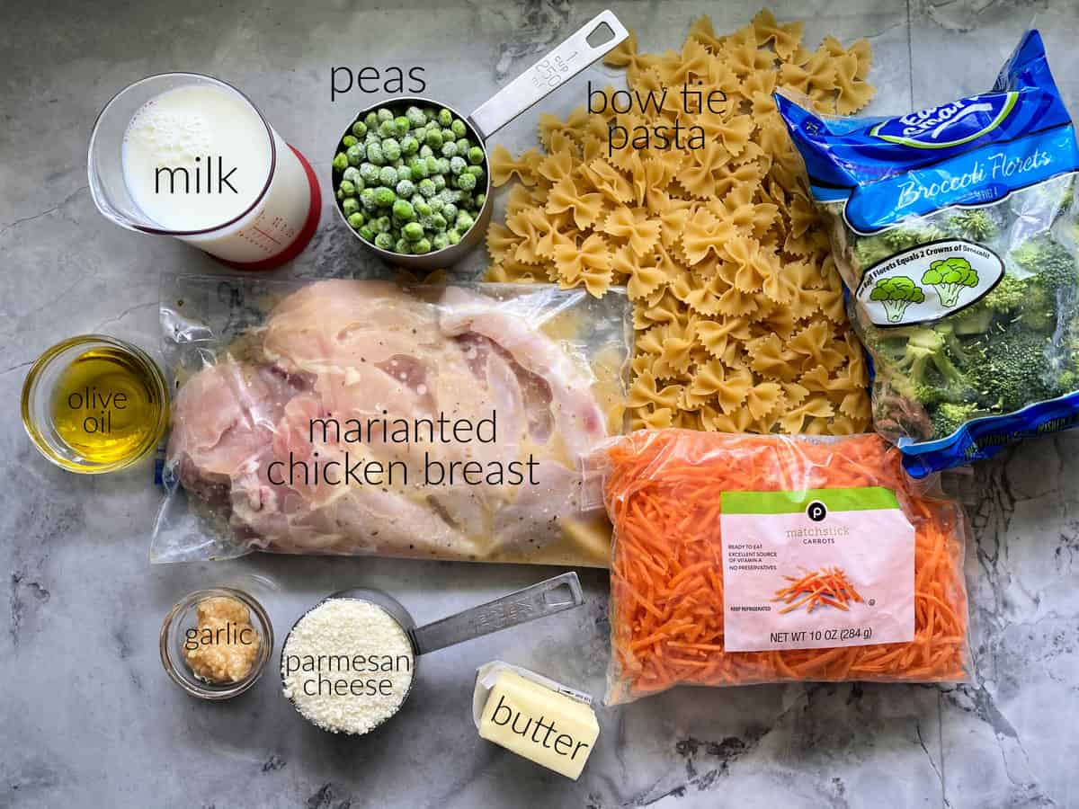 Ingredients on counter: pasta, chicken breast, carrots, broccoli, butter, parmesan, garlic, olive oil, milk, and peas.