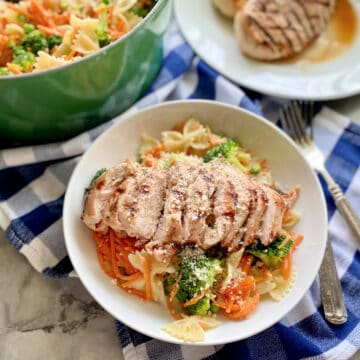Bowl filled with bow tie pasta with shredded carrots, broccoli, and grilled chicken with a green pot and plate of chicken in the background.
