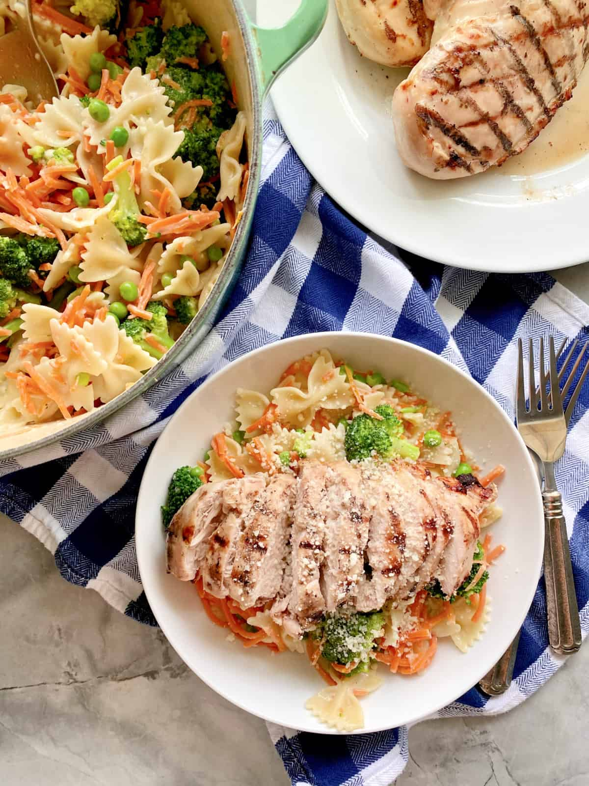 Top view of a bowl of Grilled Chicken Pasta with vegetables, a large pot with bow tie pasta and veggies and a plate of grilled chicken breast.