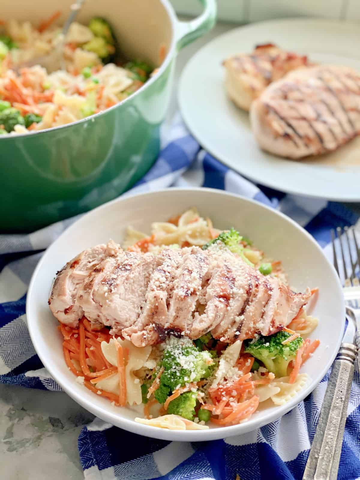 Bowl full of Grilled Chicken Pasta with veggies with a plate of chicken breast in background.