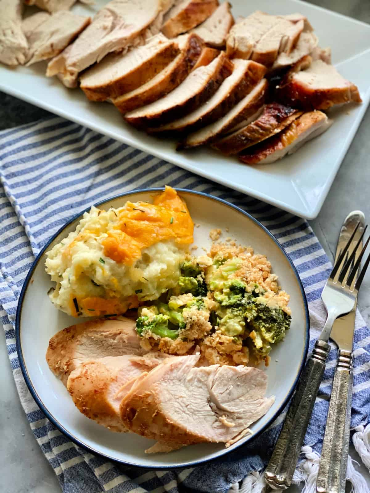 Top view of sliced turkey breast, mashed potatoes, and broccoli casserole with silverware on the side and platter of turkey next to the plate.