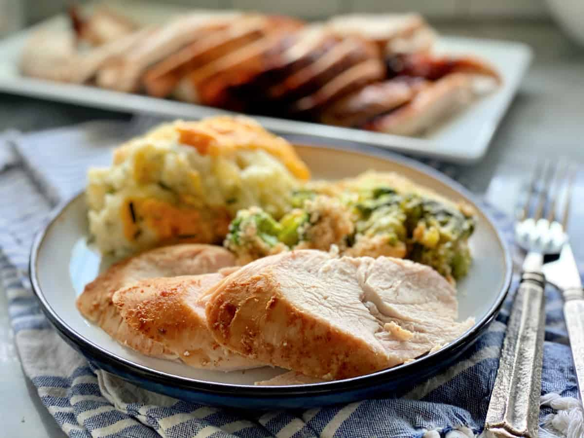 Three slices of turkey breast on a plate filled with side dishes with silverware and napkin on the side.