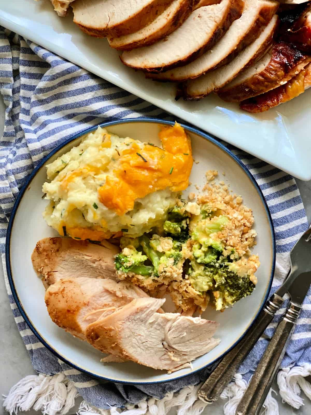 Top view of a plate filled with three slices of turkey bresat, mashed potatoes, and casserole with a platter of sliced turkey on the side.