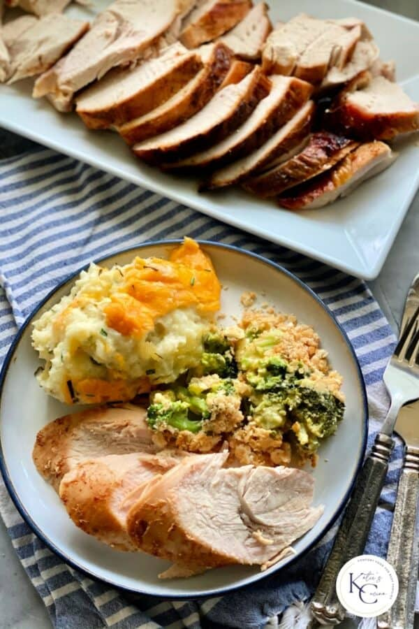 Top view of a white plate filled with turkey breast slices with mashed potatoes and broccoli casserole with a platter filled with sliced turkey breast.
