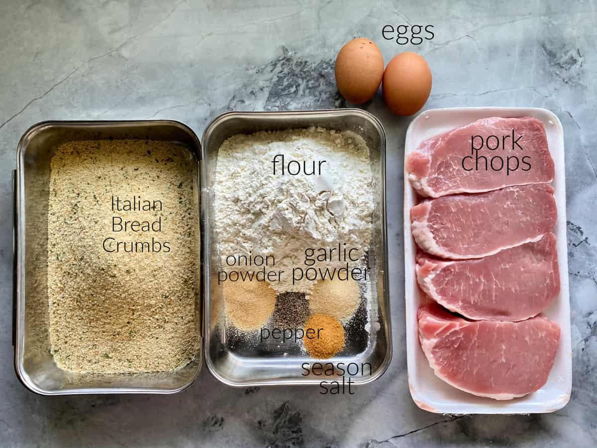Ingredients on counter; eggs, flour, pork chops, bread crumbs, flour, garlic powder, onion powder, and season salt.
