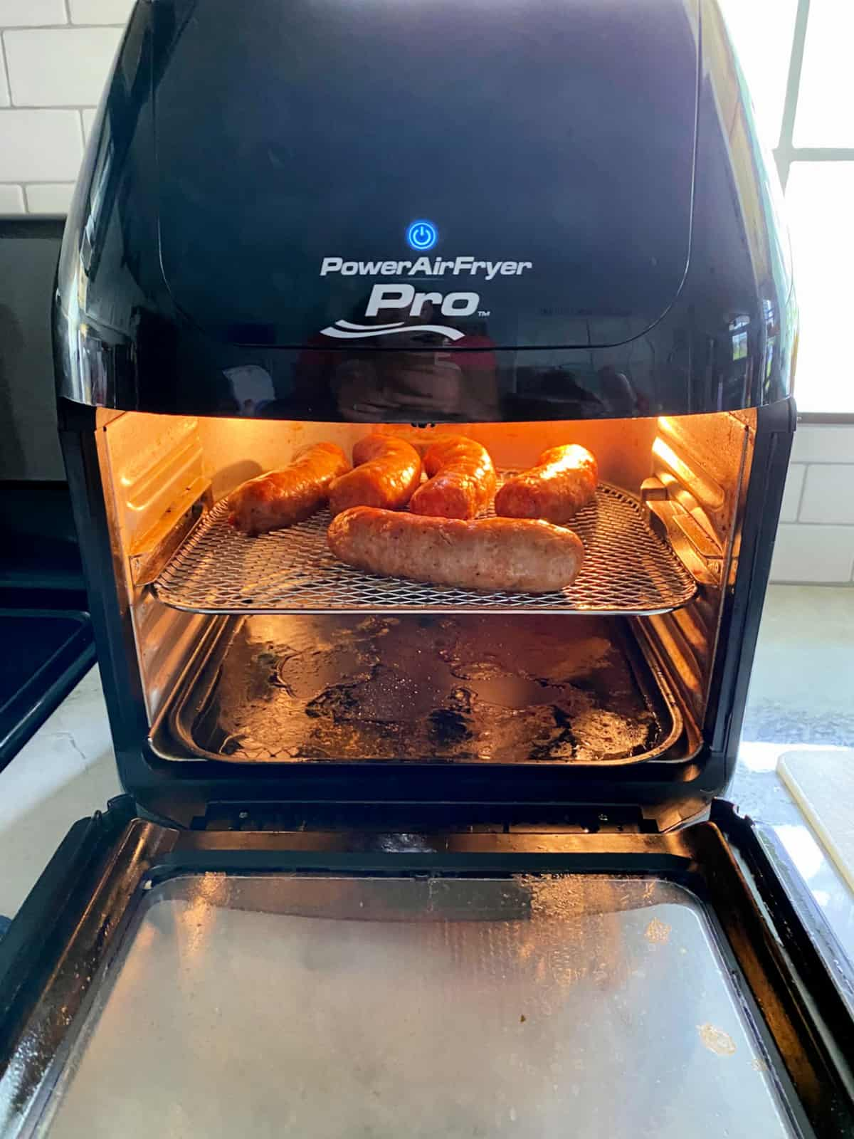 Power Air Fryer Pro with a wire rack full of sausage links inside the oven.