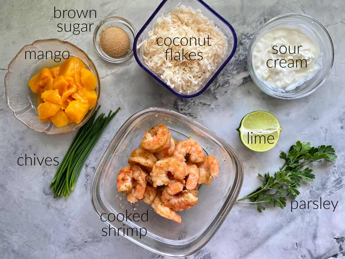 Ingredients on countertop: mango, brown sugar, chives, shrimp, coconut flakes, sour cream, lime, parsley.