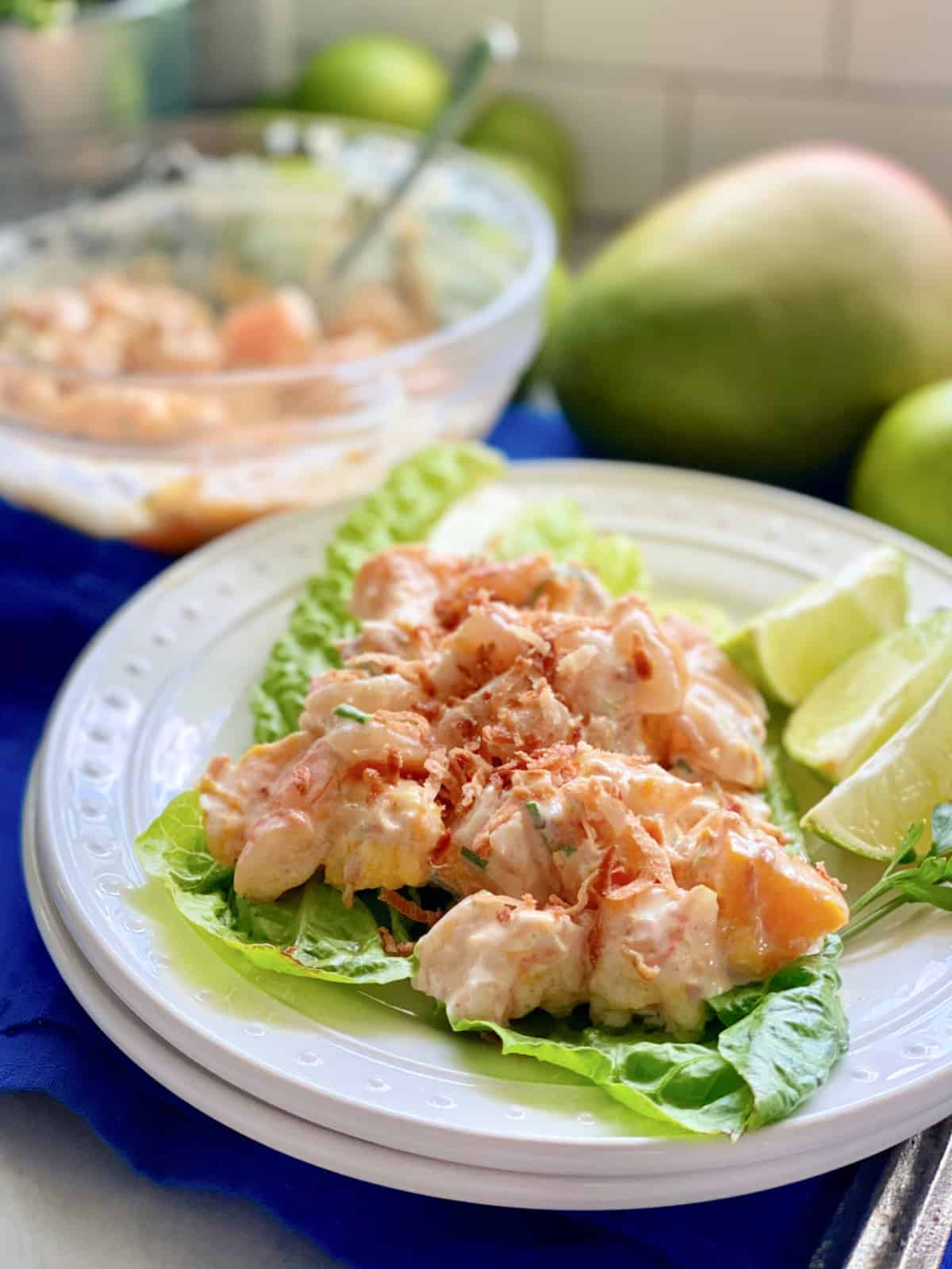 White plate with lettuce and Mango Shrimp Salad on top.