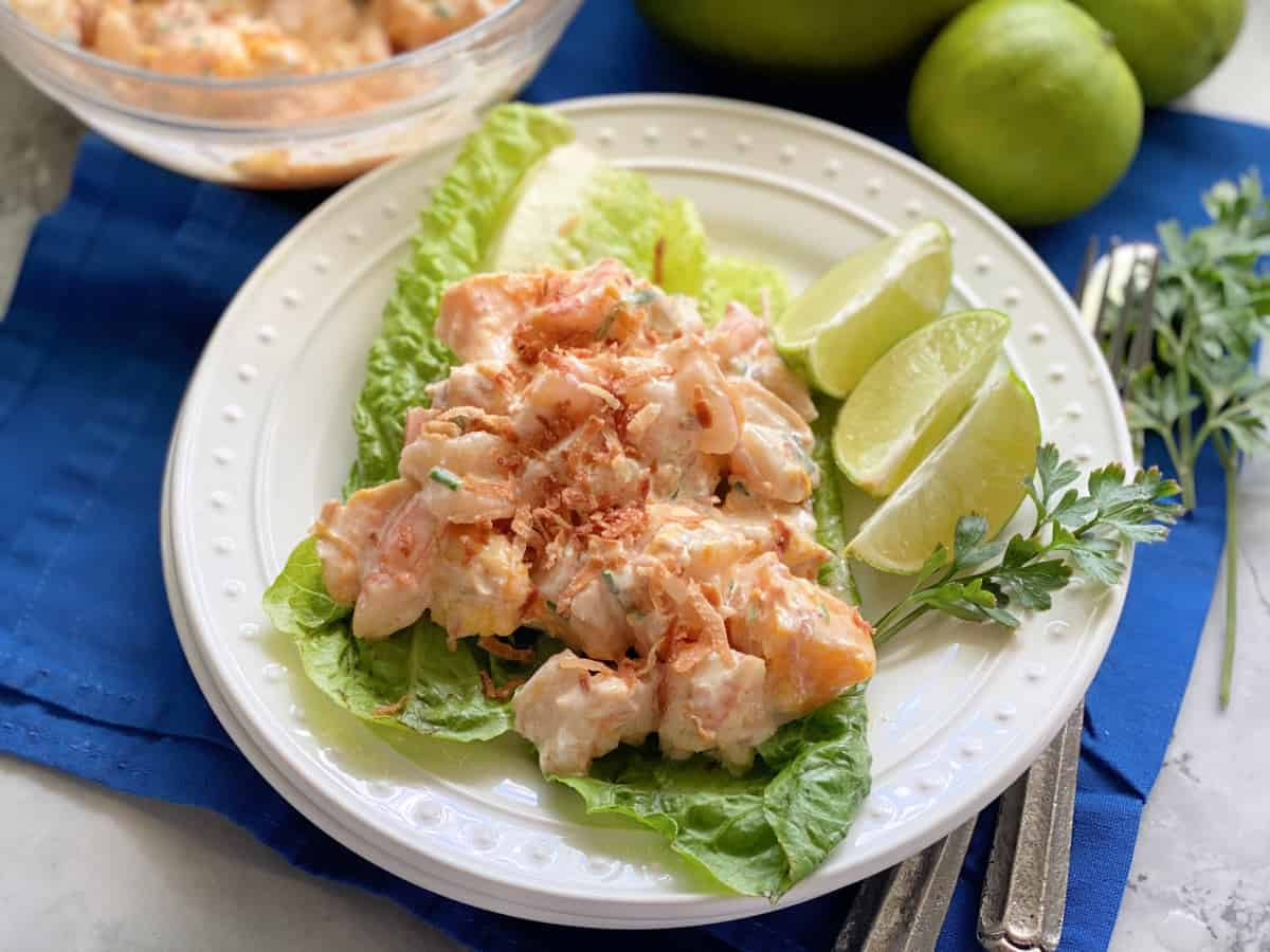 White plate with lettuce leaves and shrimp with sauce.