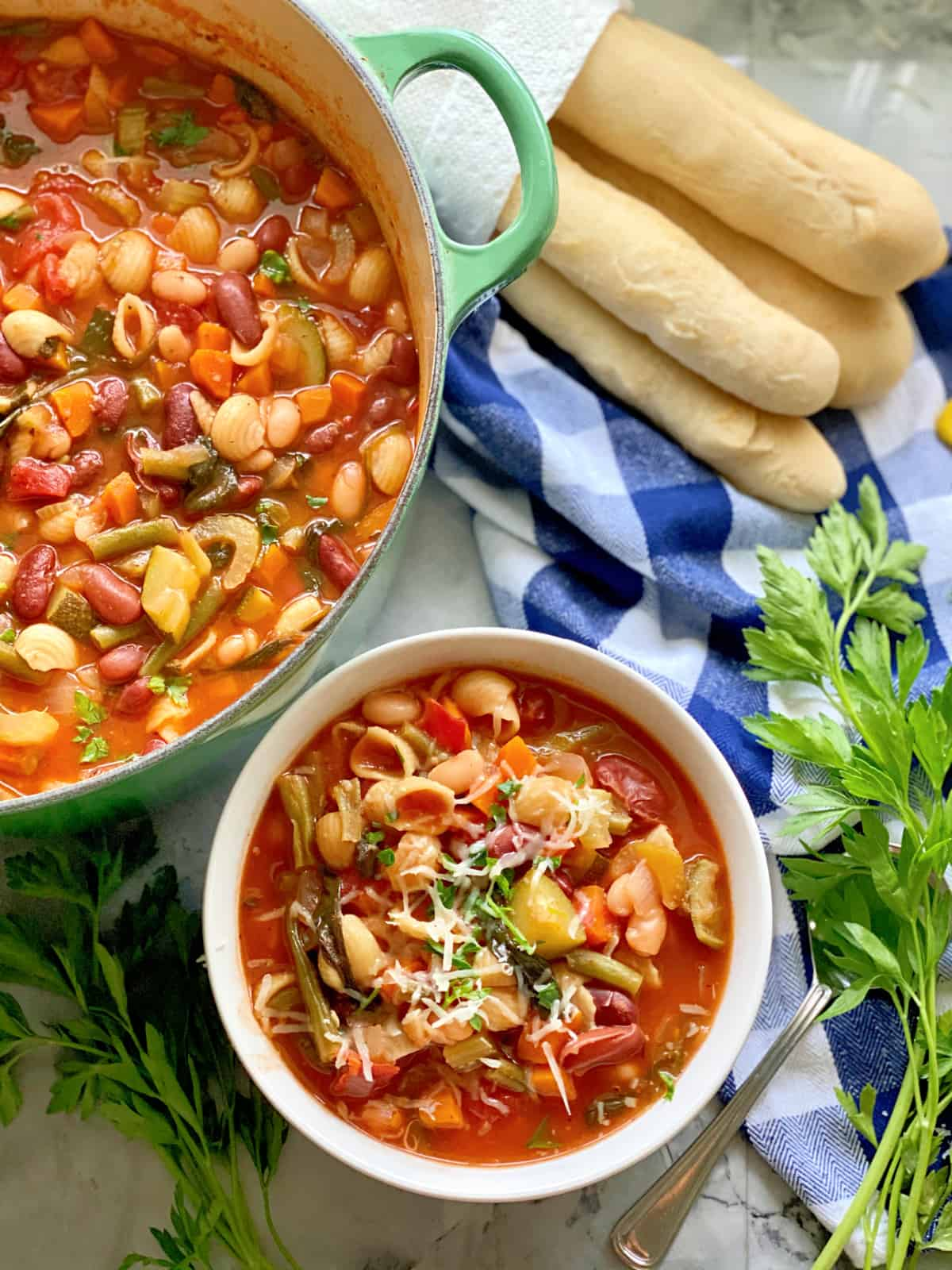 Top view of a large pot filled with minestrone soup with a bowl filled with soup and breasticks next to it.