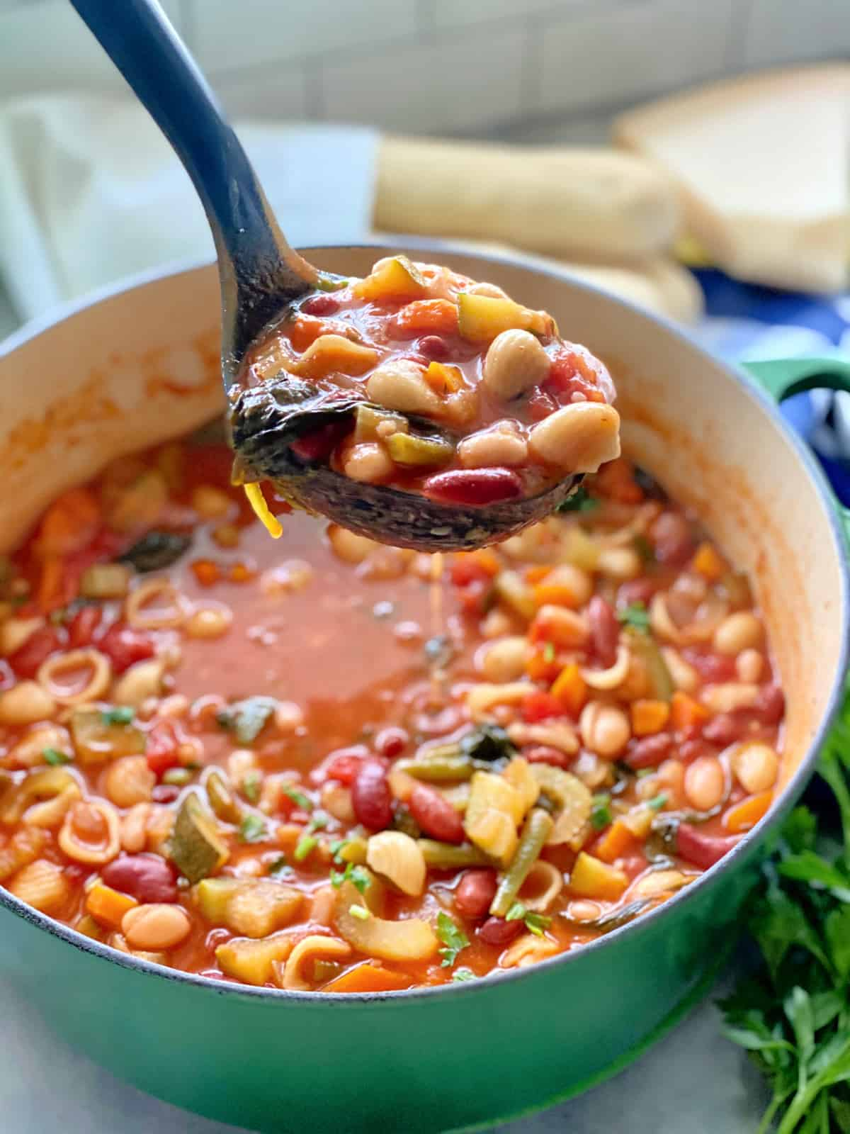 Green pot filled with minestrone soup and a black ladle filled with minestrone over the pot.