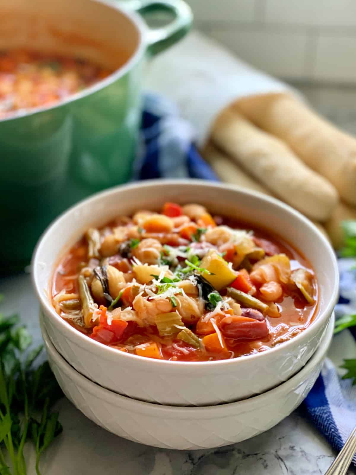 Two white bowls filled with minestrone soup with green pot and breadsticks in the background.