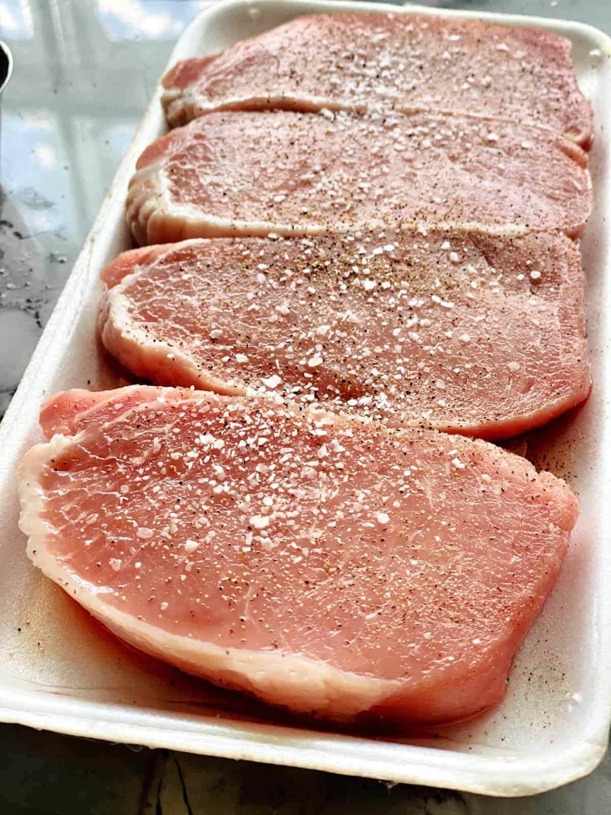 Four boneless porkchops seasoned on a white styrofoam tray.